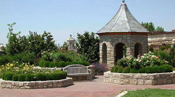 Brick paths leading to flowerbeds, a bench and a sandstone gazebo in the Idaho Botanical Garden's English Garden.