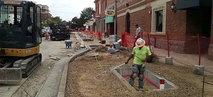 construction workers tearing up sidewalk for redesign project